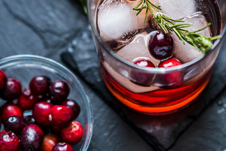 Cranberry juice cocktail with bowl of cranberries on slate